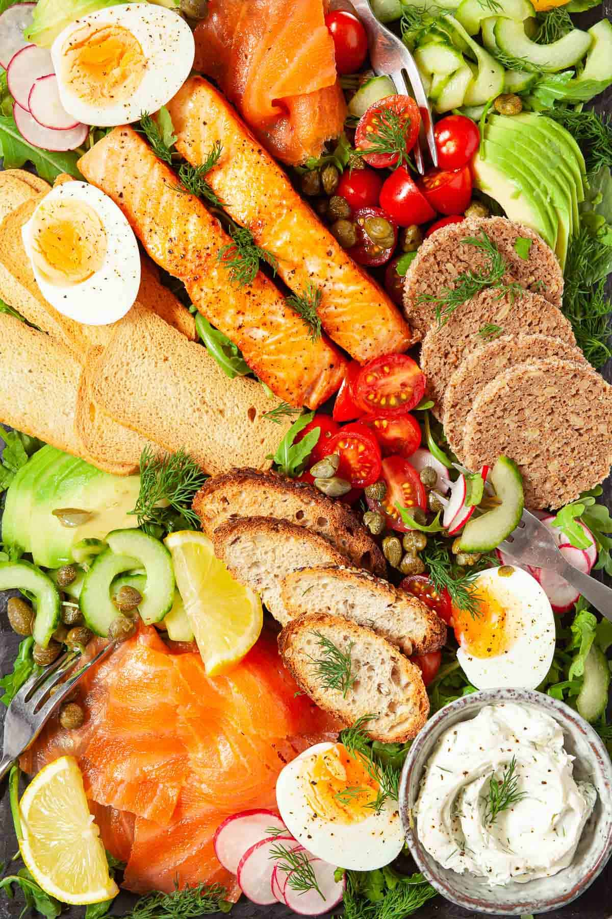 Close up of a salmon breakfast platter with eggs, vegetables and toasts