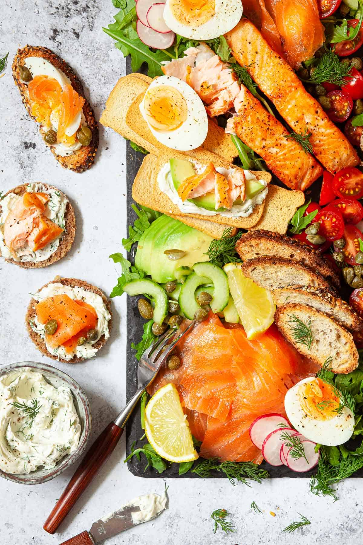 A salmon platter with assembled toasts at the side made from ingredients from the platter