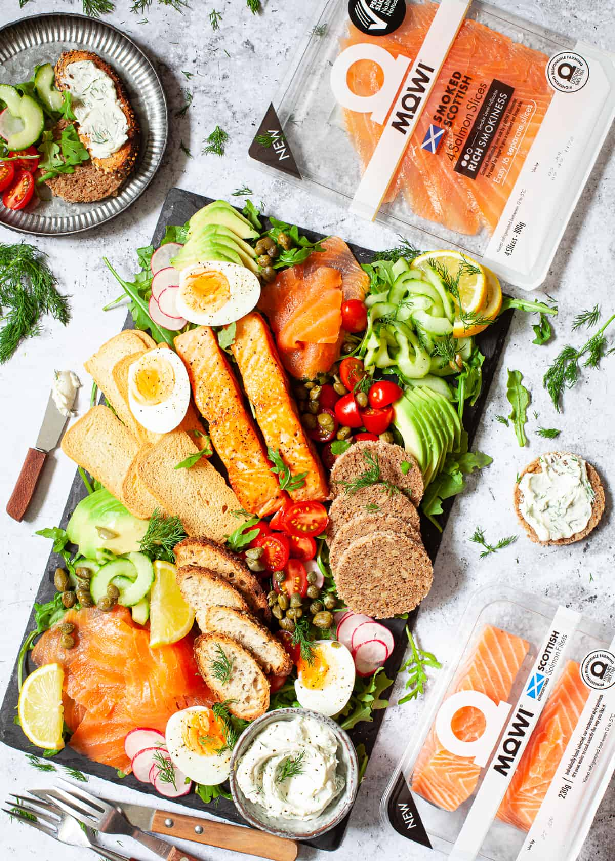A platter of fresh vegetables, eggs, fish and various breads and toasts