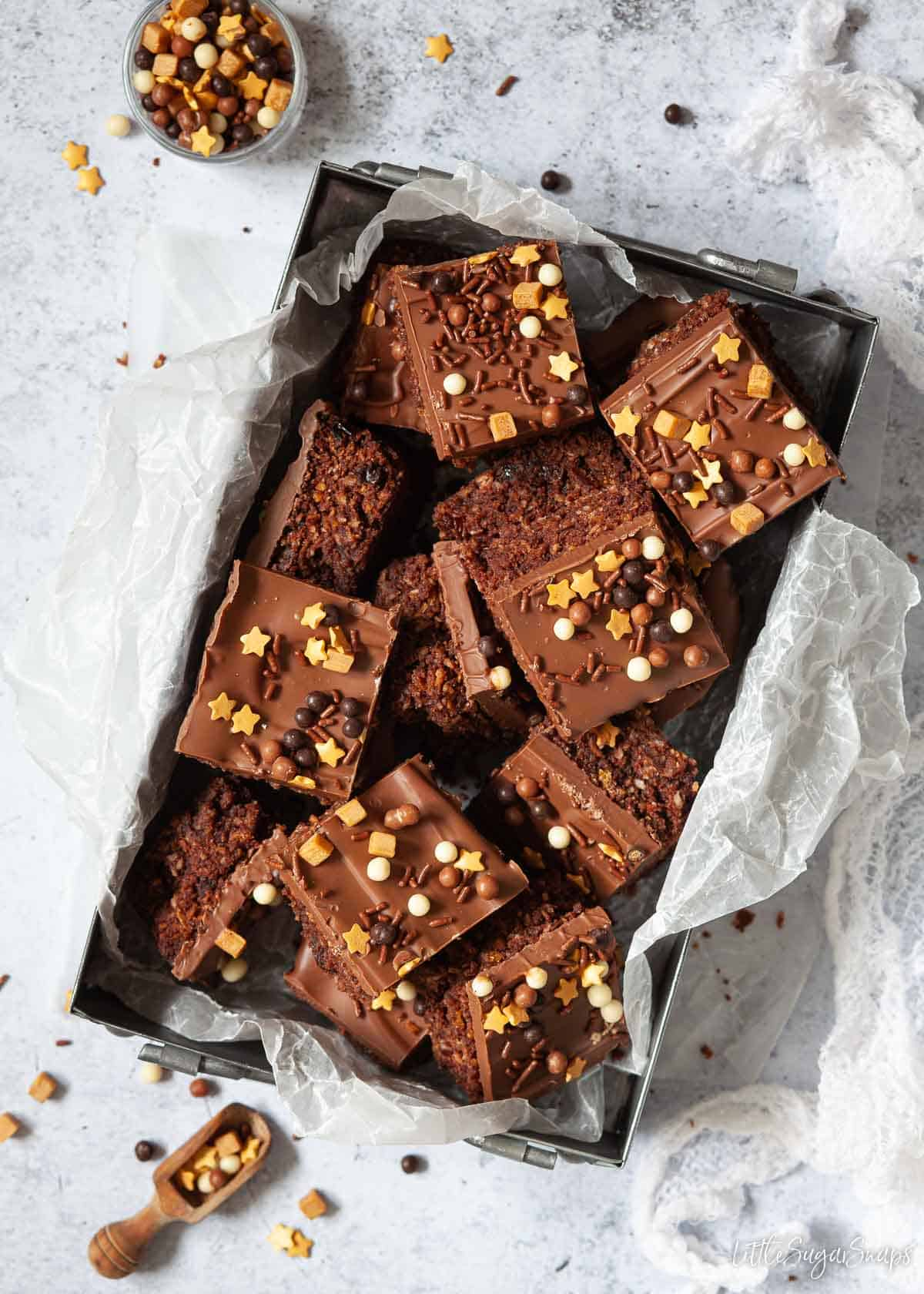 A tin of Australian Crunchie bars topped with chocolate and sprinkles