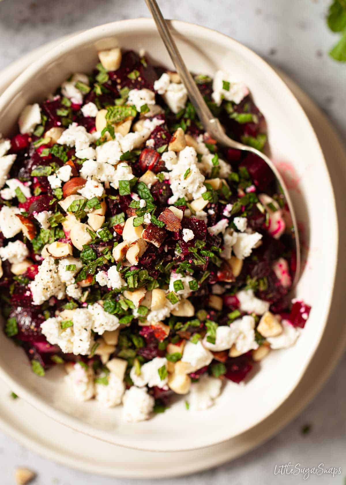 A bowl of mixed beetroot salad featuring cubed beets, crumbled feta, chopped mint and chopped nuts.