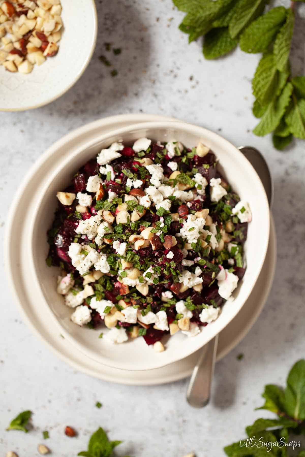 A bowl of beetroot and feta cheese in a bowl with a serving spoon alongside
