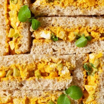 Close up of Coronation Chicken Sandwiches on brown bread with watercress garnish