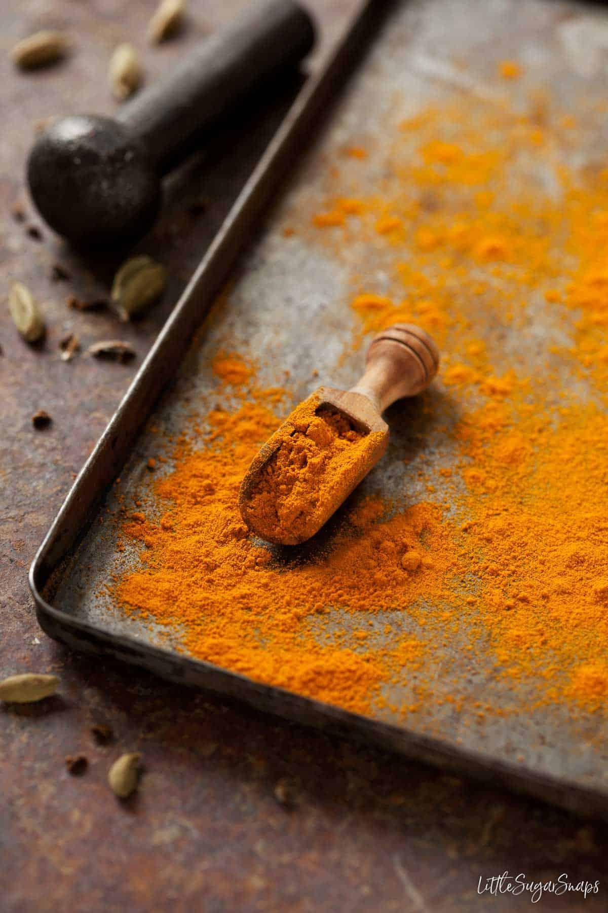Ground turmeric spice on a baking tin