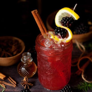 A blackberry bramble garnished with lemon and fresh fruit
