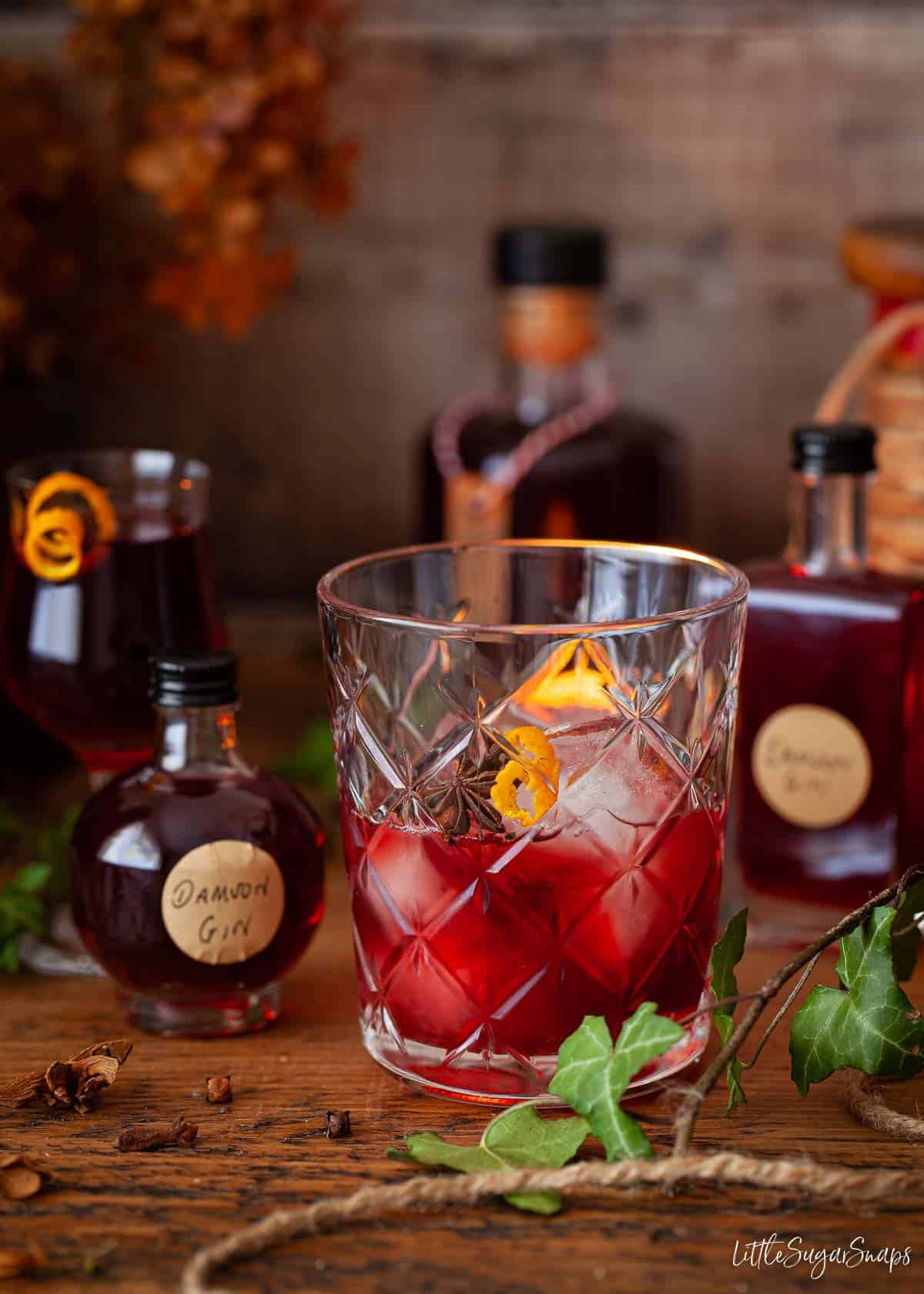 A serving of damson gin liqueur served over ice with an orange zest garnish