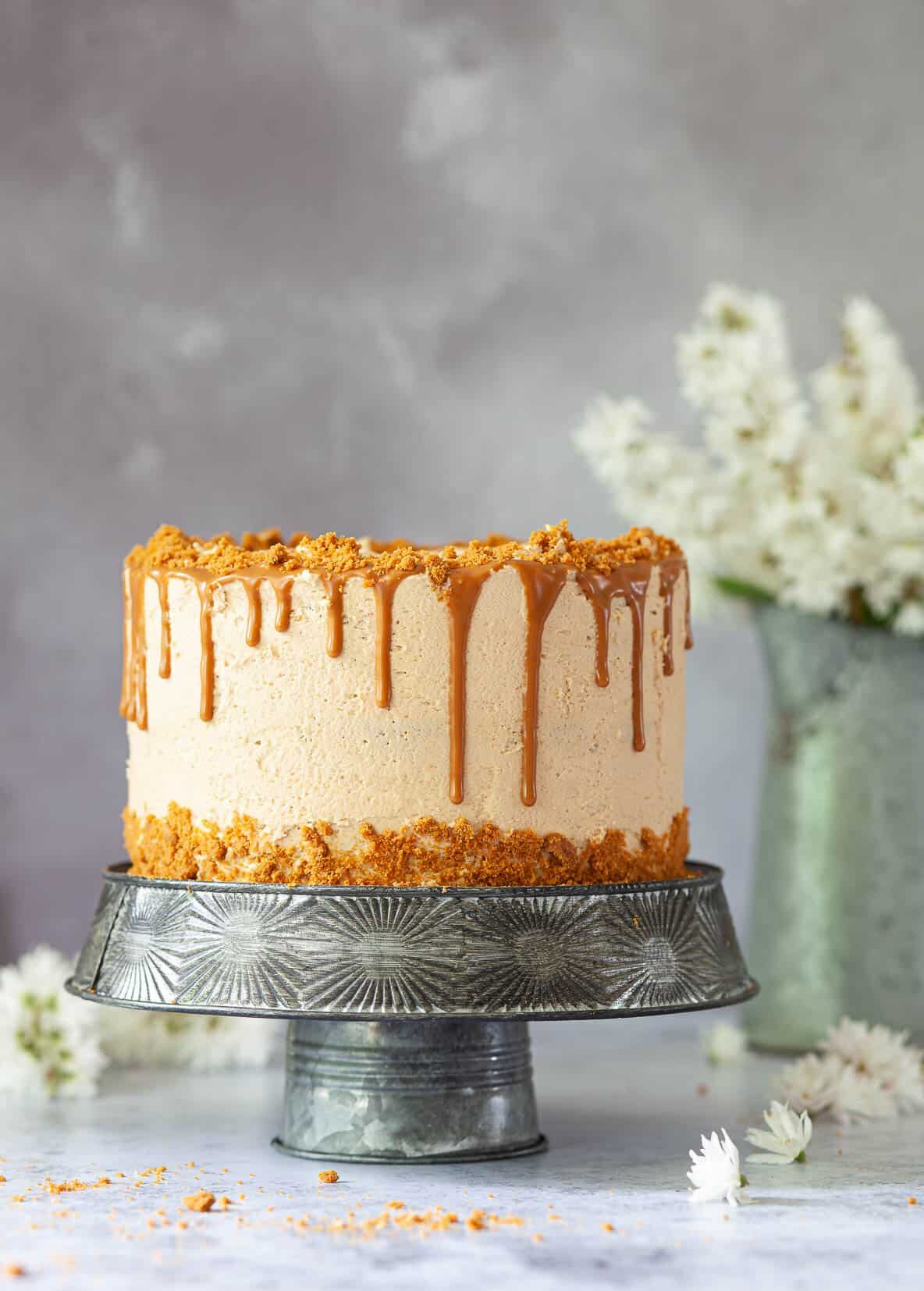 Vegan Biscoff drip cake decorated with buttercream, crushed cookies and Biscoff drip