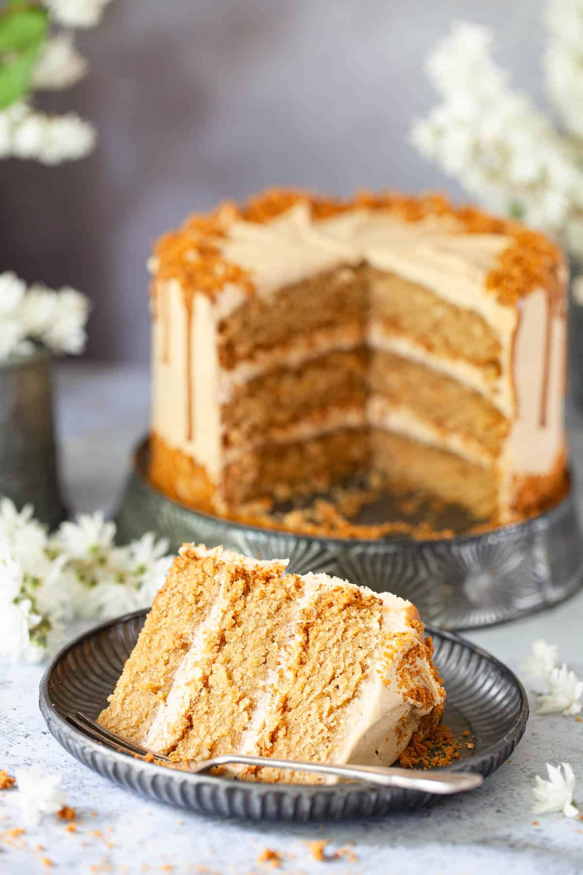 A slice of vegan Biscoff cake with Biscoff buttercream in front of the entire cake
