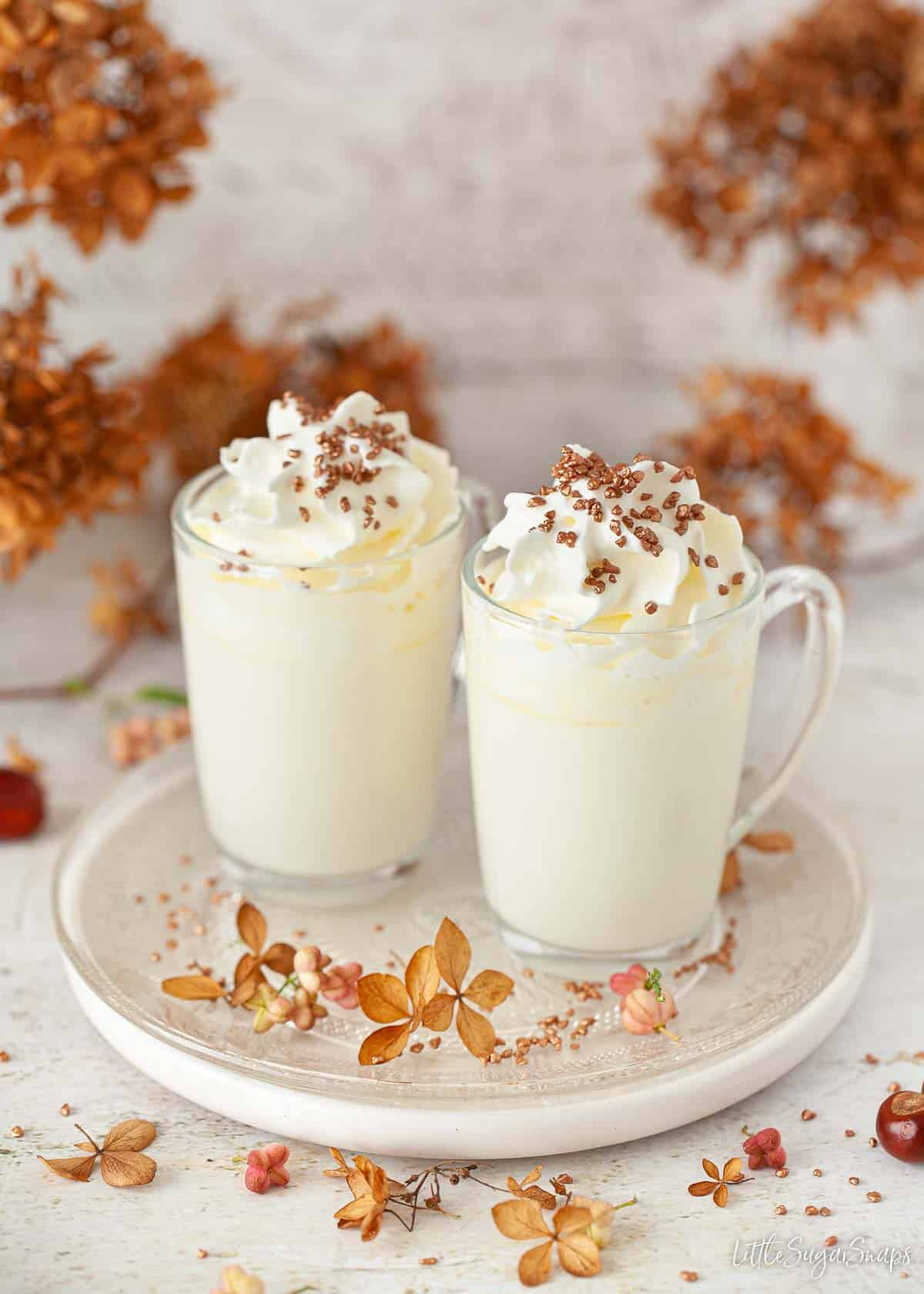 Two glass mugs of white hot chocolate with cream and bronze sprinkles