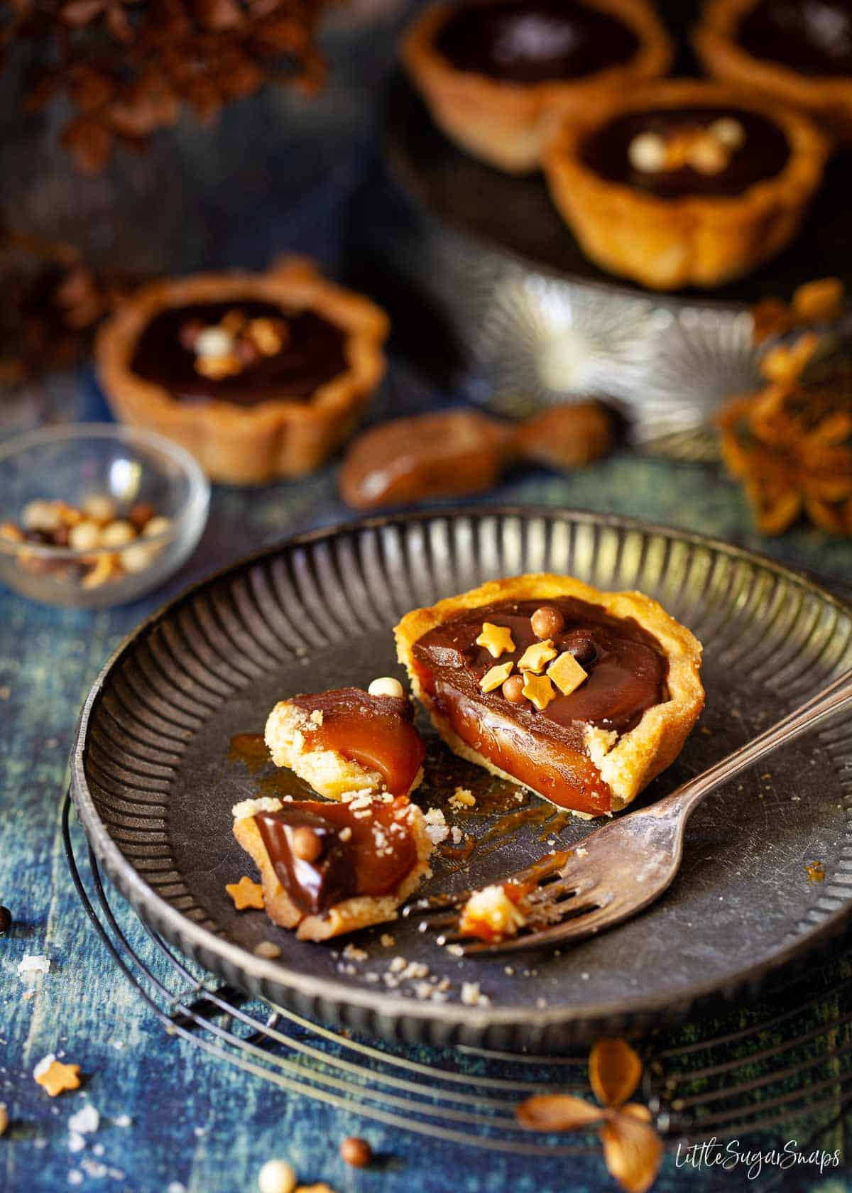 A cut-open mini caramel tart on a metal plate with more tarts in the background.