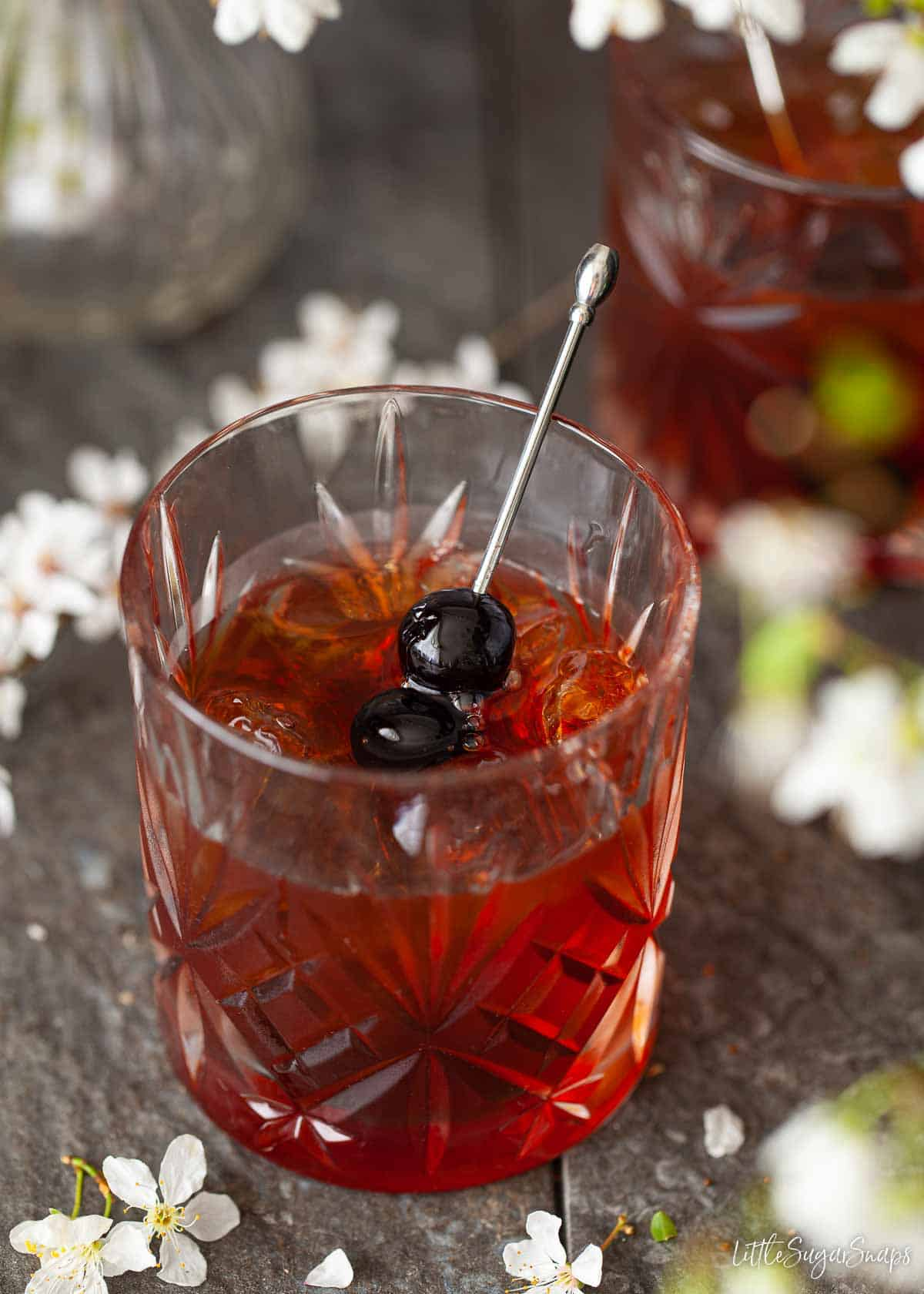 A cocktail made with bourbon whisky and amaro bitter garnished with dark cocktail cherries.