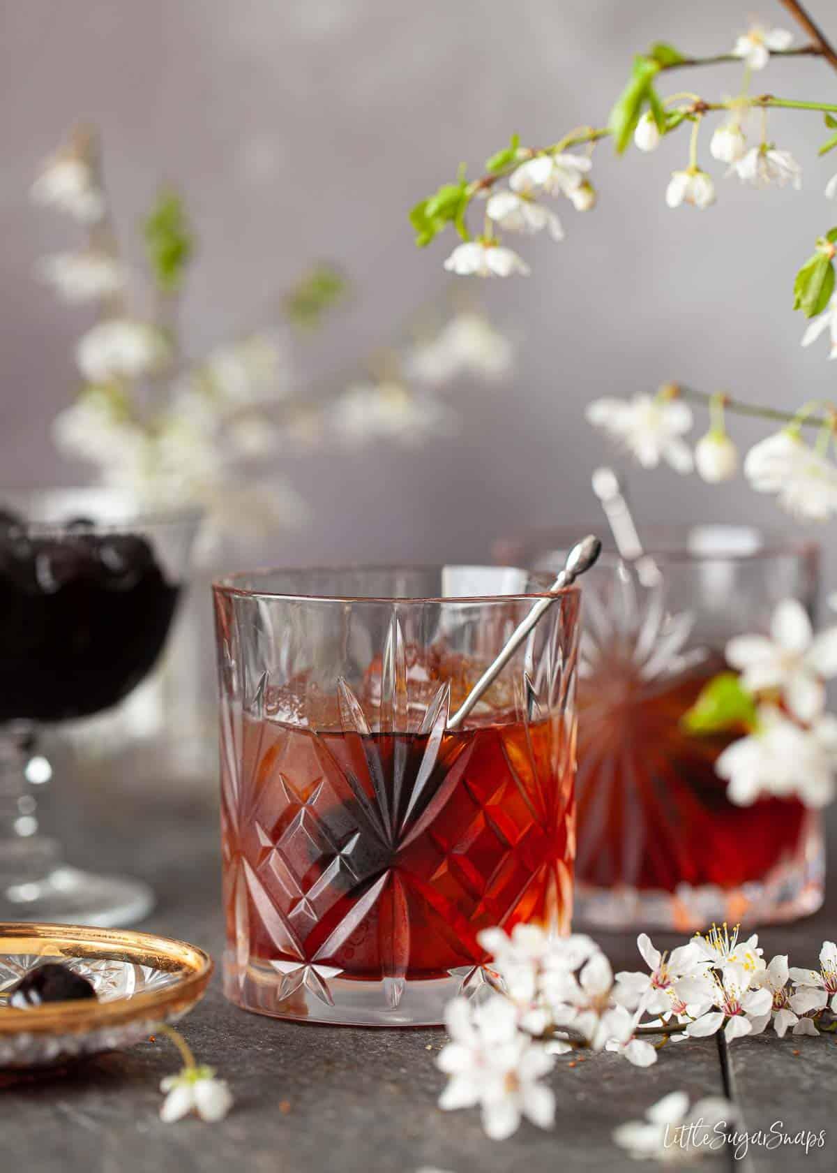 An amaro averna cocktail with dark cherries as a garnish.