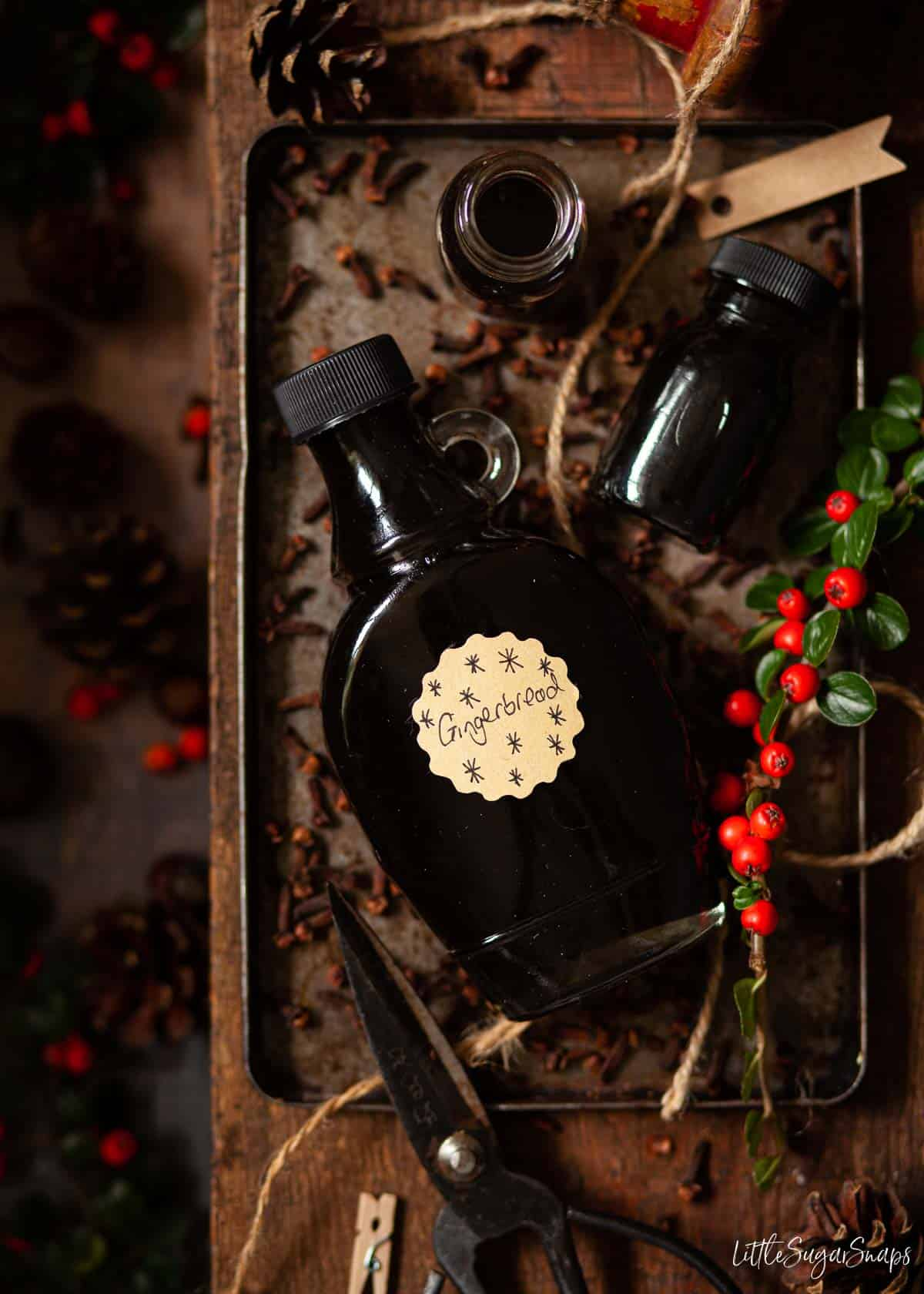 Bottles of gingerbread latte syrup on a tin tray with cloves.