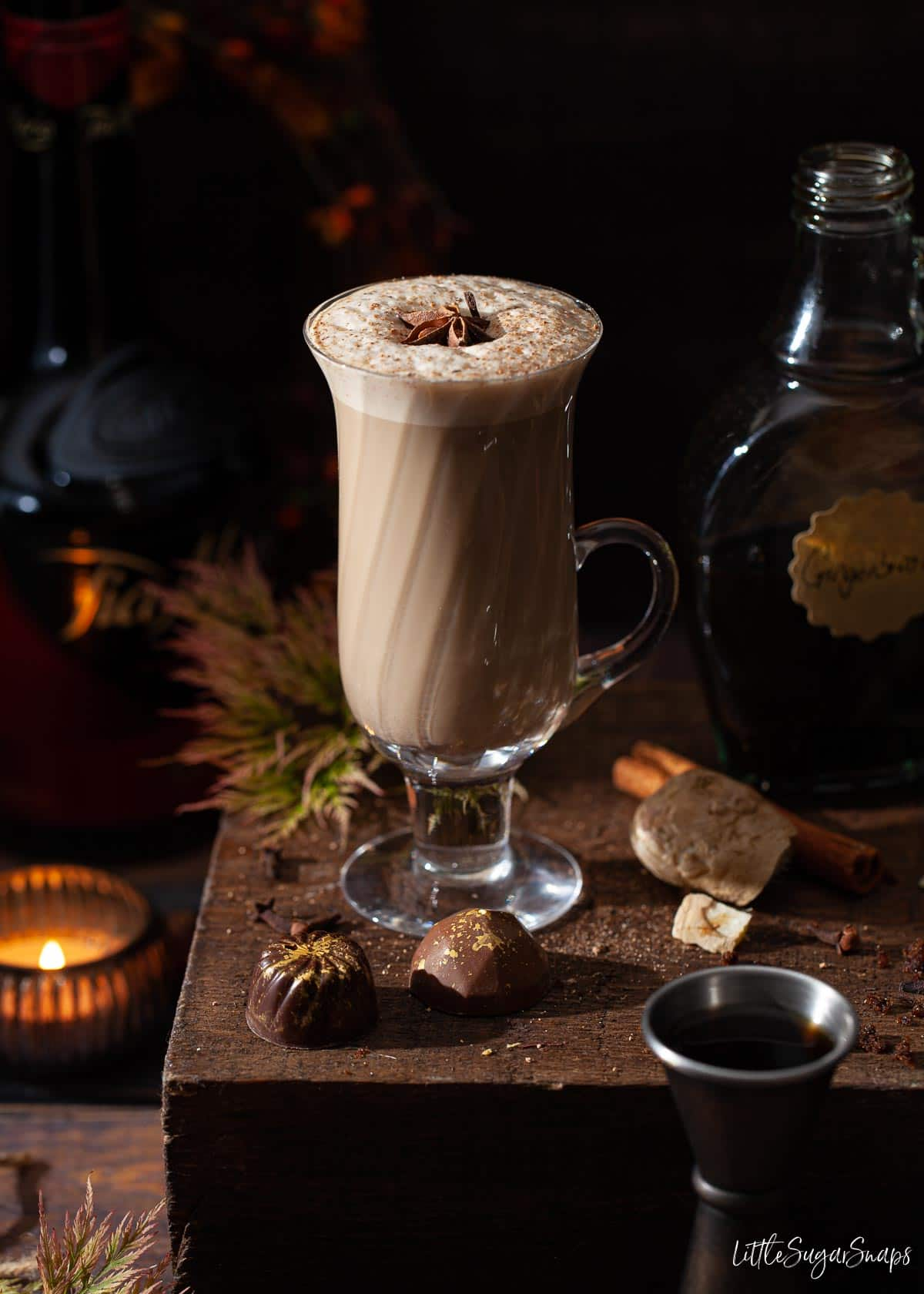 A glass of Christmas gingerbread spiced latte with frothy milk on top.