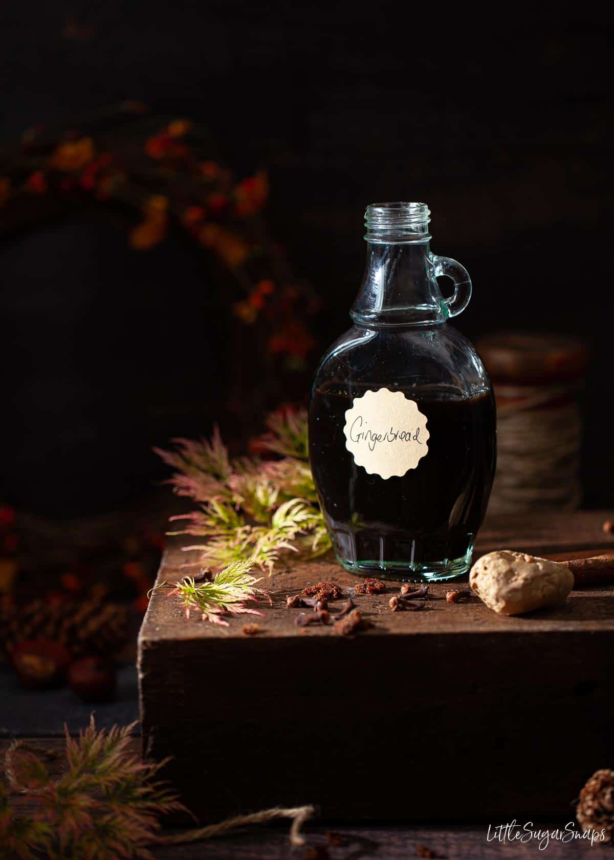 A bottle of homemade gingerbread syrup with autumn foliage in the image.